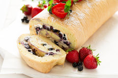 Biscuit roll with mascarpone cream and blueberries decorated strawberries, blueberries and mint leaves Stock Photo