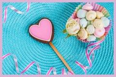 Biscuit rose de pain d'épice sous forme de coeur sur le fond de turquoise Foyer mou sélectif, traitement en pastel Images stock