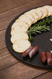 Biscuit, rosemary and sausages on slate board Royalty Free Stock Photos