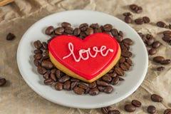 Biscuit rouge de Valentine avec amour des textes d'un plat avec des grains de café Image libre de droits