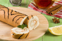 Biscuit swiss roll with a cup of tea on green wooden background Royalty Free Stock Photo