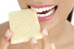 Biscuit in woman teeth and mouth, healthy snack Stock Image