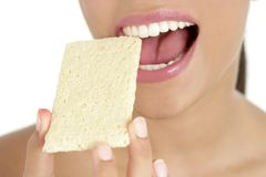 Biscuit in woman teeth and mouth, healthy snack Royalty Free Stock Photo
