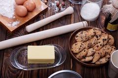 Biscuits à côté des ingrédients et des ustensiles de cuisson sur un fond en bois Concept fait maison de cuisson image stock