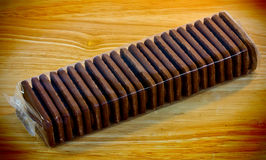 Bourbon biscuits. Bourbon  biscuits wrapped in cellophane on a wooden background Royalty Free Stock Photos