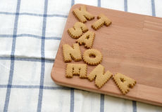 Biscuits ABC on wooden plate Stock Photos