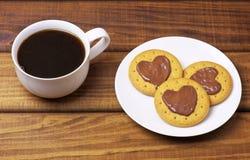 Biscuits avec des coeurs de chocolat d'un plat et d'une tasse de café Photographie stock libre de droits