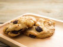 Biscuits avec des noisetiers de chocolat et d'Australie Placé sur un plat en bois Image libre de droits