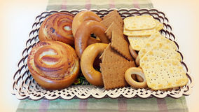 Biscuits, bagels, rolls in a basket on the table. A variety of baked goods: cookies, crackers, bagels, muffins in the basket on the table Stock Photo