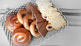 Biscuits, bagels, rolls in a basket on the table. A variety of baked goods: cookies, crackers, bagels, muffins in the basket on the table Royalty Free Stock Photo