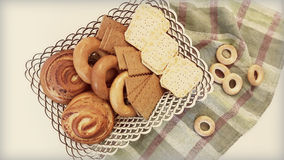 Biscuits, bagels, rolls in a basket on the table. A variety of baked goods: cookies, crackers, bagels, muffins in the basket on the table Royalty Free Stock Image