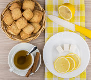 Biscuits in basket, hot tea, lemon, sugar cubes and knife Royalty Free Stock Photo