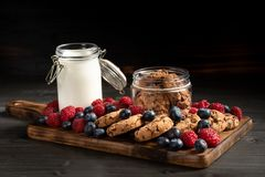 Biscuits, berries and milk on wooden bottom, side view. royalty free stock images