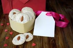 Biscuits blancs avec l'amande dans la boîte en forme de coeur Image libre de droits