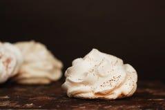 Biscuits blancs de meringue Désert doux au-dessus de Brown Rusty Wooden Board dans le plat noir photographie stock