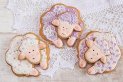 Biscuits blancs et pourpres de pain d'épice de moutons sur le fond de dentelle Image stock