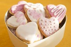 Biscuits blancs et roses avec le givrage sous forme de coeur en BO Images libres de droits