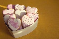 Biscuits blancs et roses avec le givrage sous forme de coeur en BO Image libre de droits