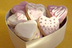Biscuits blancs et roses avec le givrage sous forme de coeur en BO Photo libre de droits