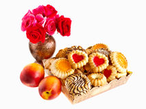 Biscuits in a box, nectarines and roses. Biscuits in a box, nectarines and a bouquet of roses Stock Image