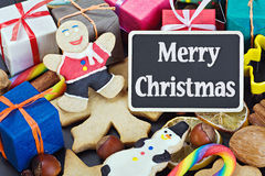 Biscuits for Christmas and a black board with a greeting for the. Sweets and biscuits for Christmas and a black board with a greeting for the holiday Stock Image