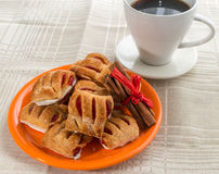 Biscuits with cinnamon sticks on orange plate Stock Images