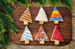 Biscuits colorés d'arbre de Noël sur un fond en bois foncé image stock