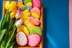 Biscuits colorés de lapin et d'oeufs de Pâques dans un panier sur un Ba en bois photo stock