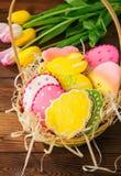 Biscuits colorés de lapin et d'oeufs de Pâques dans un panier sur un Ba en bois photographie stock