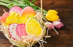 Biscuits colorés de lapin et d'oeufs de Pâques dans un panier sur un Ba en bois photos libres de droits