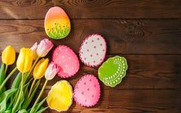 Biscuits colorés de lapin et d'oeufs de Pâques dans un panier sur un Ba en bois images stock
