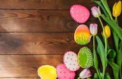 Biscuits colorés de lapin et d'oeufs de Pâques dans un panier sur un Ba en bois photo libre de droits