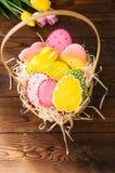 Biscuits colorés de lapin et d'oeufs de Pâques dans un panier sur un Ba en bois images libres de droits