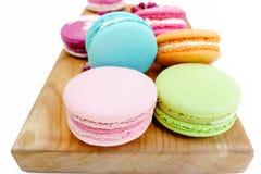 Biscuits colorés de macaron gastronome sur le bureau en bois D'isolement sur le fond blanc Image libre de droits