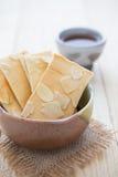 Biscuits coupés en tranches d'amande dans le bol et une tasse de thé chaud sur W Photographie stock