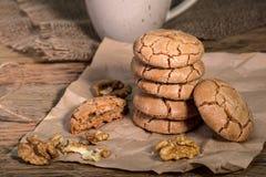 Biscuits criqués caoutchouteux de noix avec une tasse de café sur le bois rustique images stock