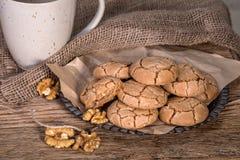 Biscuits criqués caoutchouteux de noix avec une tasse de café sur le bois rustique photo stock