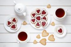 Biscuits d'amoureux pour le jour de valentines avec la théière et deux tasses de composition de thé sur le fond en bois blanc Image libre de droits