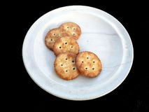 Biscuits dans le plat blanc d'isolement sur le fond noir photos stock