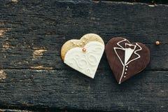 Biscuits décorés du mariage sur le fond en bois Image libre de droits