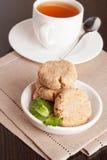 Biscuits de beurre de noix de coco avec la tasse de thé Image stock