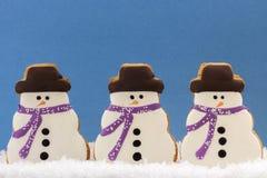 Biscuits de bonhommes de neige sur le bleu Image libre de droits