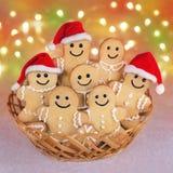 Biscuits de bonhommes en pain d'épice de Noël dans des chapeaux de Santa contre les lumières b Photo stock