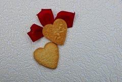 Biscuits de Brown et pétales de rose rouges sur une table grise Photographie stock libre de droits