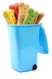 Biscuits de chien dans une poubelle bleue Photos libres de droits