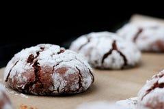 Biscuits de chocolat avec des fissures sur le papier de cuisson et iolated sur le noir Biscuits criqués de chocolat photographie stock libre de droits