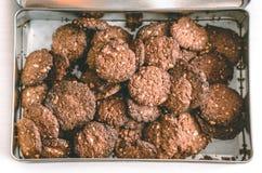 Biscuits de chocolat d'avoine faits maison dans la boîte en métal sur la table blanche Photo stock