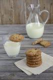 Biscuits de chocolat et de canneberge avec du lait sur la table en bois Images libres de droits