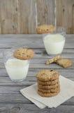 Biscuits de chocolat et de canneberge avec du lait sur la table en bois Photos libres de droits