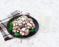Biscuits de chocolat et un verre de lait sur le fond blanc Photographie stock